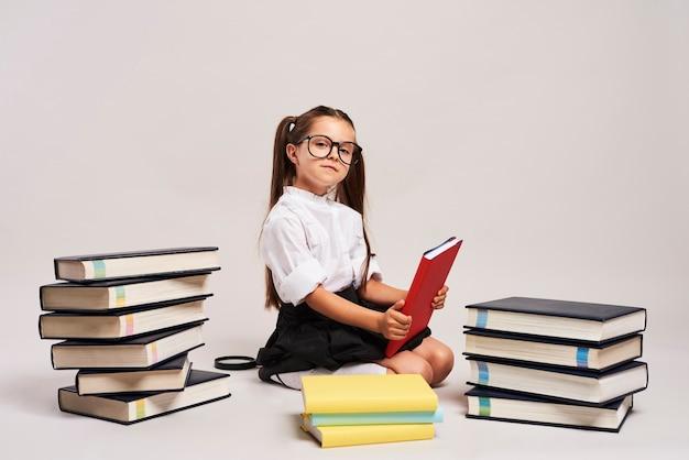 책 사이에 앉아 자신감이 소녀