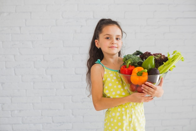 Confident girl standing in front of wall holding bowl of vegetables Free Photo