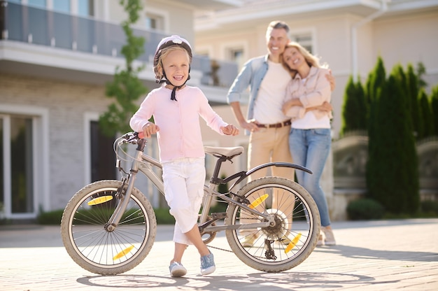 Confident girl with bike and happy parents