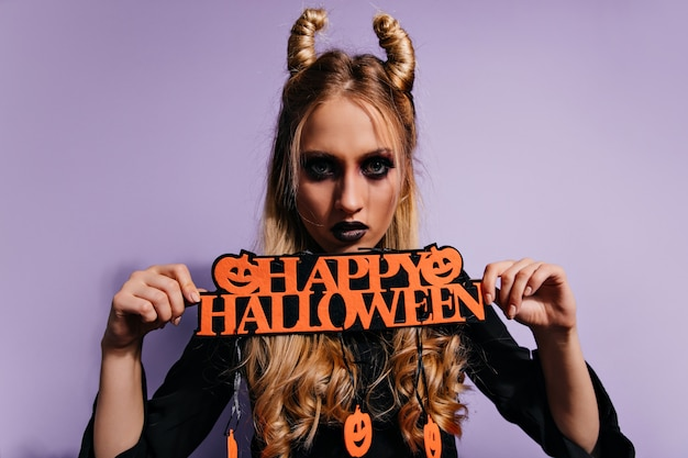 Confident girl with scary black makeup posing before party.  serious blonde woman in vampire costume celebrating halloween.