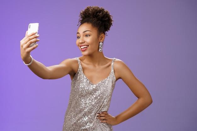 Уверенно рада привлекательной стильной афроамериканской миллениалке в серебряном блестящем платье, делающей селфи, позирующей милой нахальной рукой, за талию, вытягивающую руку, записывающую видео-сообщение во время вечеринки.