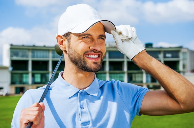 Уверенный игрок в гольф. низкий угол обзора молодого счастливого гольфиста, держащего водителя и регулирующего его кепку, стоя на поле для гольфа