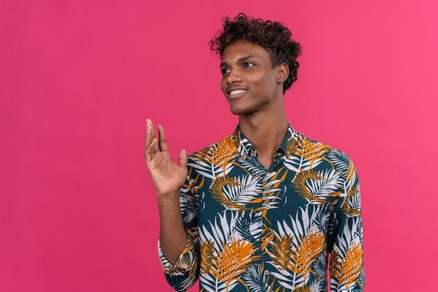 葉っぱに巻き毛があり、側面を見ながら手を上げているプリントシャツの自信に満ちた黒肌の男