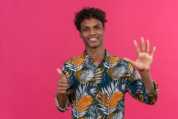 Confident good-looking dark-skinned man with curly hair in leaves printed shirt showing number six with hands