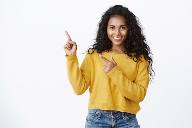 Confident good-looking girl with curly hairstyle, look camera self-assured and sassy smiling, pointing upper left corner, introduce amazing product, give recommendations