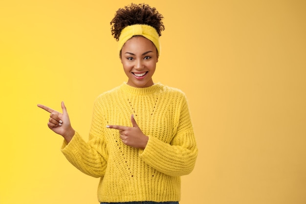 Confident good-looking millennial feminine african-american woman headband sweater look self-assured assertive pointing left index fingers you gonna like it smile, standing yellow background.