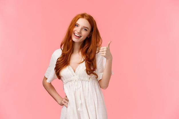 Уверенно красивая рыжая оптимистичная девушка, которая говорит, что все в порядке, все хорошо, показывает большой палец вверх и улыбается, кивает в знак одобрения, соглашается с условиями, рекомендует продукт, розовая стена