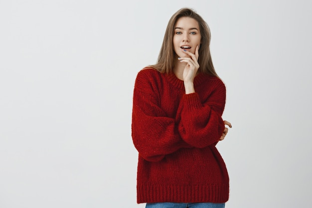 Confident good-looking sassy sexy european woman in red loose sweater biting finger looking daring and flirty , self-assured seducing with sensual gaze over