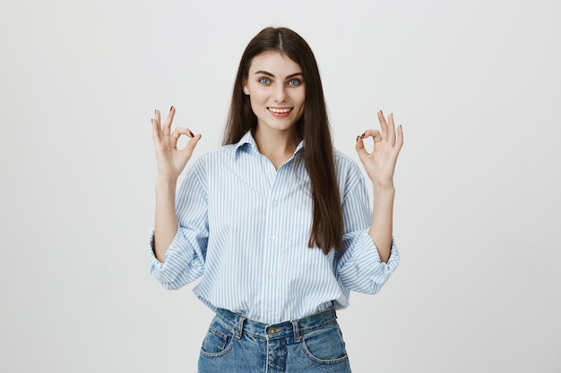 Confident good-looking woman guarantee quality, show okay sign