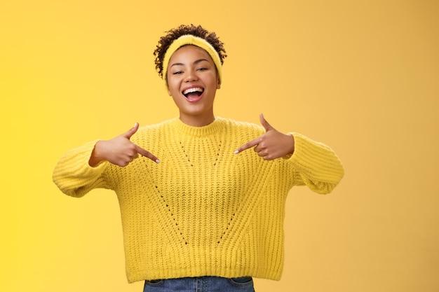 Уверенно симпатичная общительная чернокожая милая девушка в афро-прическе с повязкой на свитере показывает на себя ...