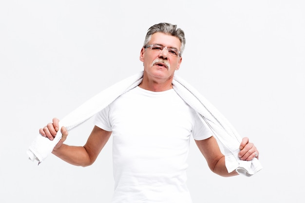 Confident grey hair senior man carrying towel on shoulders and looking at front while standing against white wall