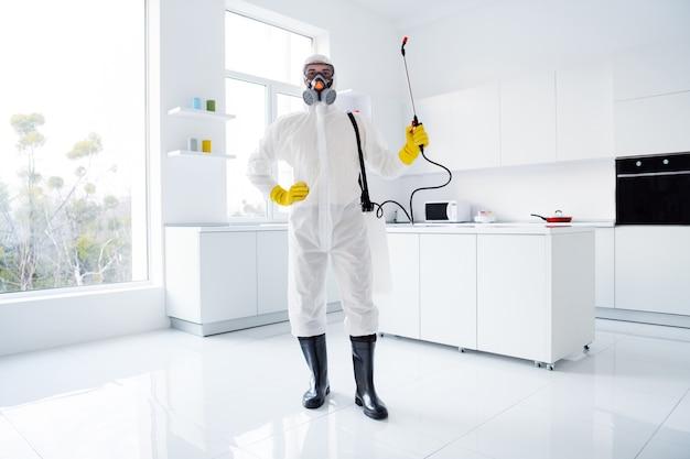 Confident guy cleaner worker in white hazmat suit