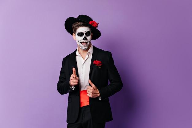 紫色の背景にポーズをとるゾンビの服装で自信を持って男。ハロウィーンパーティーを楽しんでいる格好良いデッドマン。