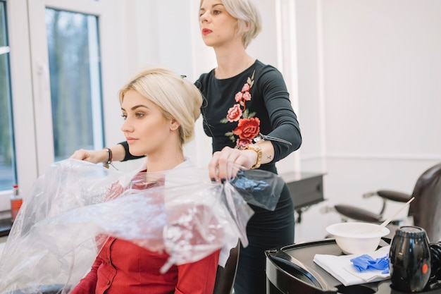 Confident hairstylist working with customer