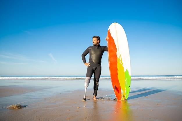 Уверенный в себе человек с ограниченными возможностями, стоящий на морском пляже с доской