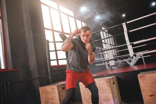 스포츠 의류를 입은 자신감 넘치는 잘 생긴 운동선수는 옆으로 돌리고 방어 동작을 연습합니다. 컬러 권투 반지 반대편에 서 있는 동안 그림자와 함께 권투 젊은 남자