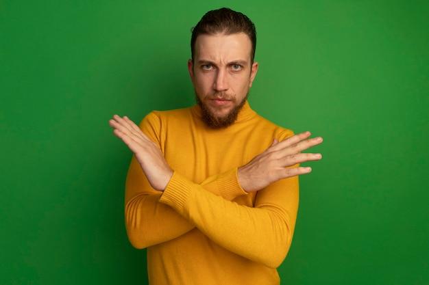 자신감이 잘 생긴 금발의 남자는 녹색에 흔적을 몸짓 손을 교차