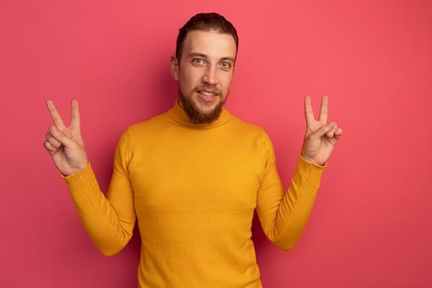 Fiducioso bell'uomo biondo gesti il segno della mano di vittoria con due mani sul rosa