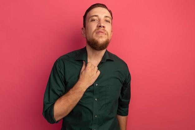 자신감이 잘 생긴 금발의 남자는 칼라를 보유하고 분홍색 벽에 고립 된 전면에 보인다