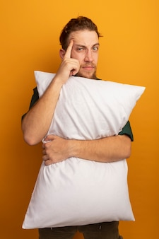 자신감이 잘 생긴 금발의 남자는 베개를 보유하고 오렌지 벽에 고립 된 사원에 손가락을 넣습니다