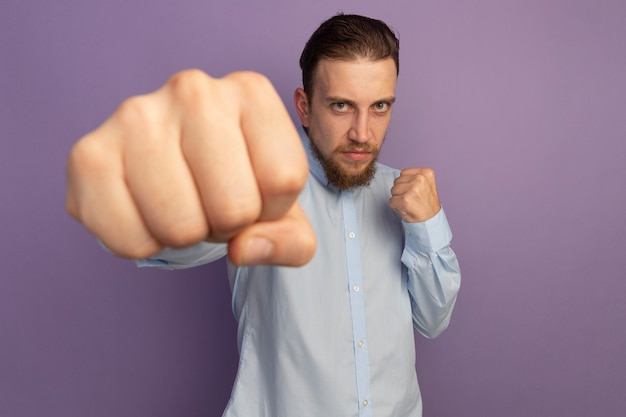 自信を持ってハンサムなブロンドの男は、紫色の壁に隔離された拳をパンチする準備ができています