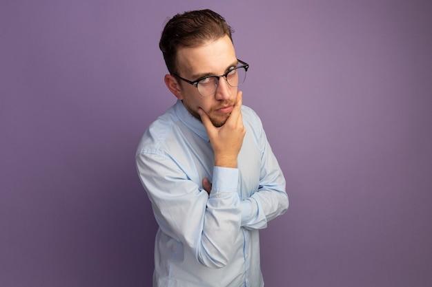 Fiducioso bell'uomo biondo in vetri ottici tiene il mento e guarda davanti isolato sulla parete viola