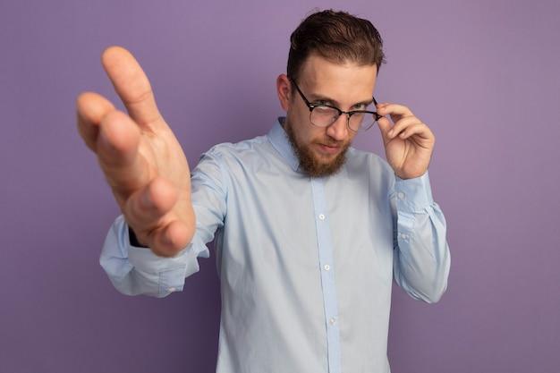Fiducioso bell'uomo biondo in occhiali da vista punta davanti con la mano isolata sulla parete viola