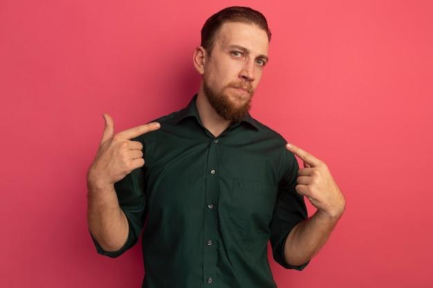 자신감이 잘 생긴 금발의 남자가 분홍색 벽에 고립 된 두 손으로 자신을 가리 킵니다.
