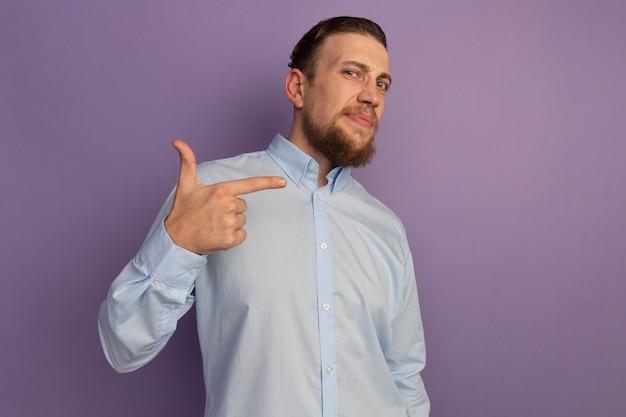 Fiducioso bell'uomo biondo punti a lato isolato sulla parete viola
