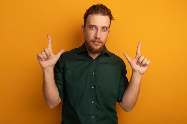 자신감이 잘 생긴 금발의 남자는 오렌지 벽에 고립 된 두 손으로 포인트