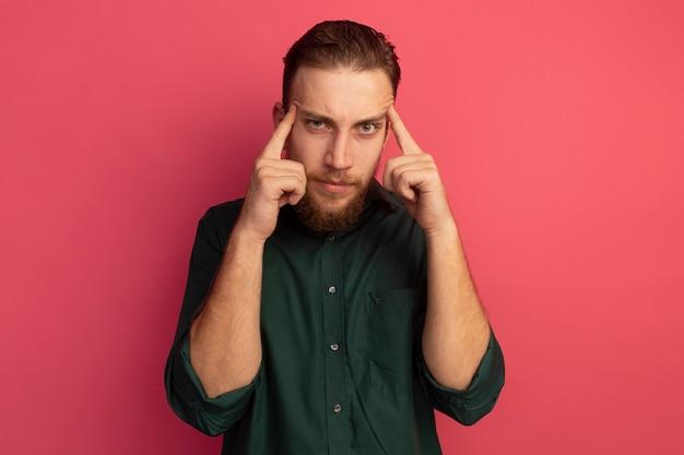 Fiducioso bell'uomo biondo mette le dita sulle tempie isolate sul muro rosa