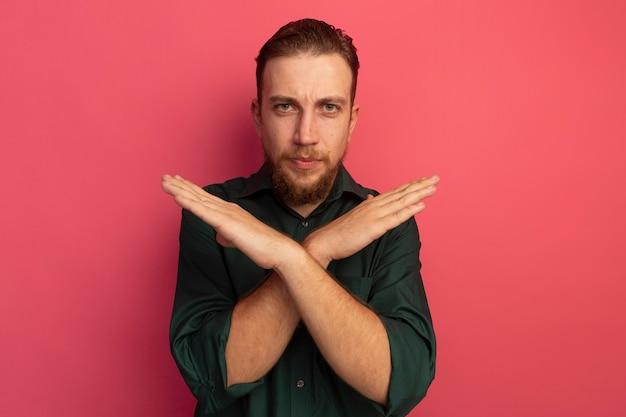 Fiducioso bell'uomo biondo sta con le mani incrociate che non gestiscono alcun segno isolato sulla parete rosa