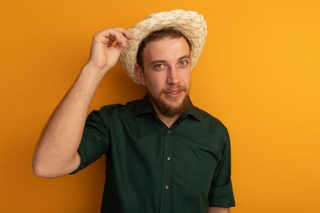 ビーチ帽子をかぶった自信を持ってハンサムなブロンドの男は、オレンジ色の壁に隔離された正面を見て