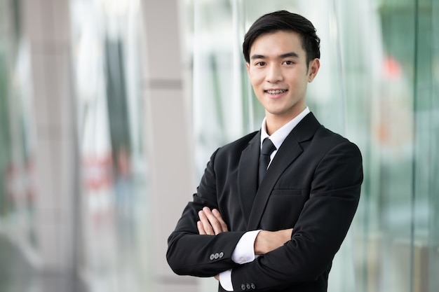 Confident handsome business man smilling in black suit standing in office