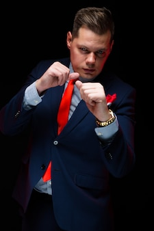 Confident handsome businessman boxing on black