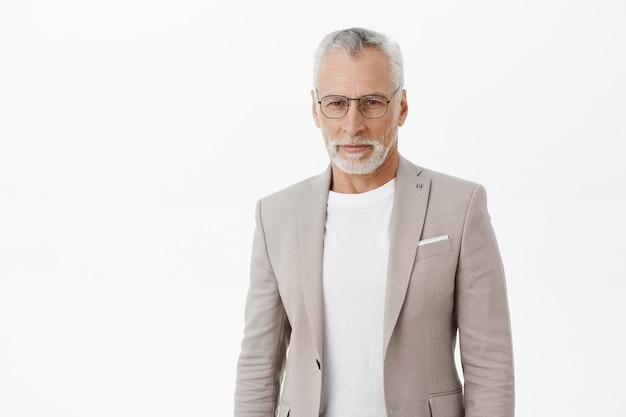 Fiducioso uomo d'affari bello in tuta e occhiali che sembrano seri
