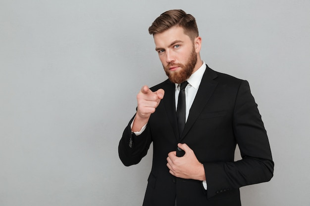 Confident handsome businessman in suit pointing finger