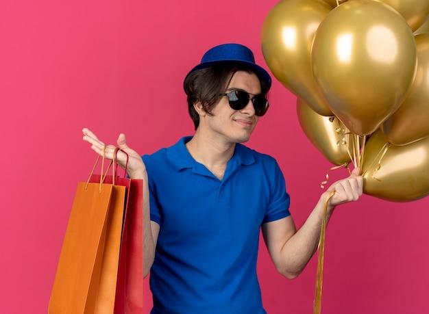 파란색 파티 모자를 쓰고 태양 안경에 자신감이 잘 생긴 백인 남자는 헬륨 풍선과 종이 쇼핑백을 보유하고 있습니다.