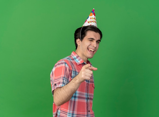 Confident handsome caucasian man wearing birthday cap blinks eye and points at camera