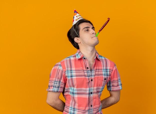 Fiducioso bell'uomo caucasico che indossa il cappello di compleanno che soffia il fischio della festa guardando il lato