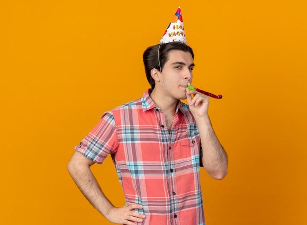 パーティーの笛を吹く誕生日の帽子をかぶった自信のあるハンサムな白人男性