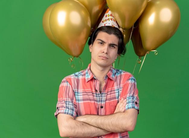 Уверенный красивый кавказский мужчина в кепке дня рождения стоит со скрещенными руками перед гелиевыми шарами, глядя в камеру