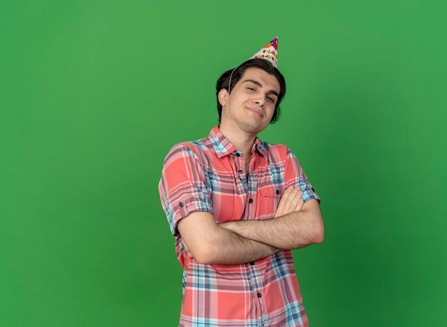 誕生日の帽子をかぶった自信に満ちたハンサムな白人男性が腕を組んで立っている