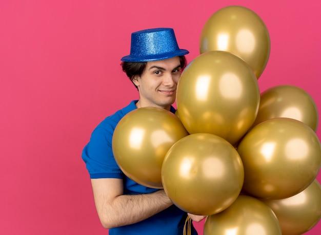 Fiducioso bell'uomo caucasico che indossa un cappello da festa blu tiene palloncini di elio