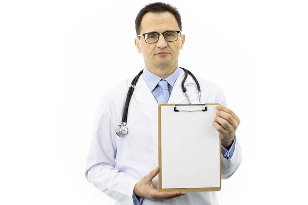 白衣と空のクリップボードを保持している聴診器で自信を持ってハンサムな医者