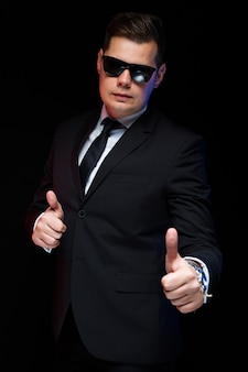 Confident handsome elegant businessman in sunglasses with thumb up showing his power and confidence