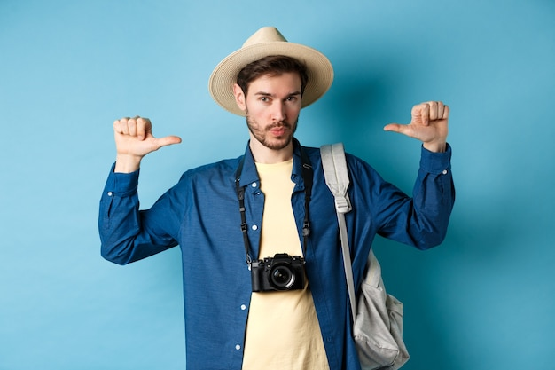 Confident handsome guy in summer hat, pointing at himself with bragging look, going to travel on holidays, holding backpack and camera, blue background.