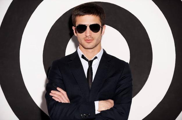 自信を持ってハンサム。黒と白の背景に立っている間腕を組んで正装のハンサムな若い男