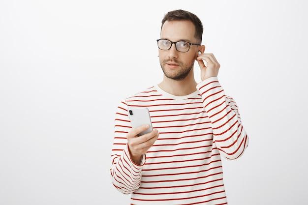 Bell'uomo fiducioso con gli occhiali neri, indossa gli auricolari wireless e tiene in mano uno smartphone bianco nuovo di zecca