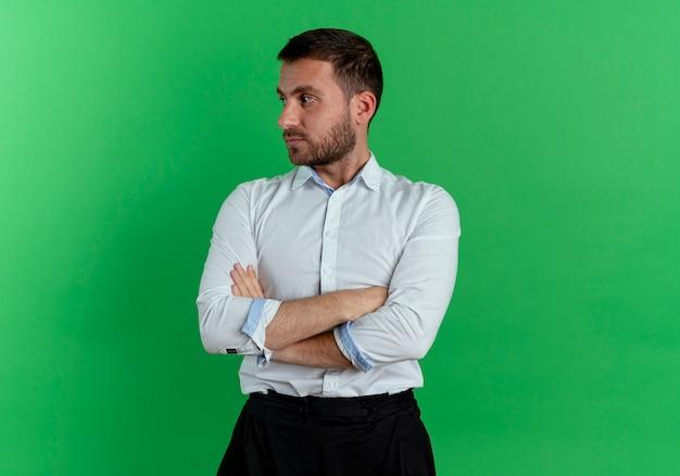 Fiducioso bell'uomo incrocia le braccia guardando il lato isolato sulla parete verde